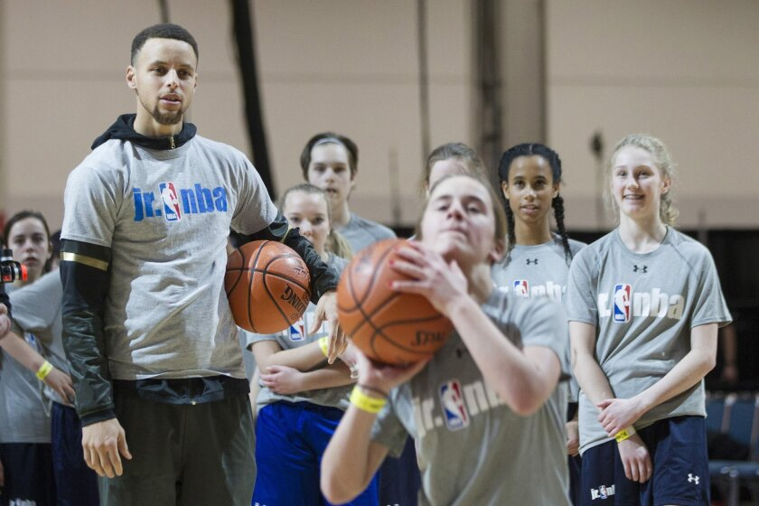 Golden State Warriors point guard Stephen Curry, front left, takes schoolchildren through a skills drill at a Jr. NBA Day event in Toronto, Friday, Feb. 12, 2016. (Chris Young/The Canadian Press via AP) MANDATORY CREDIT