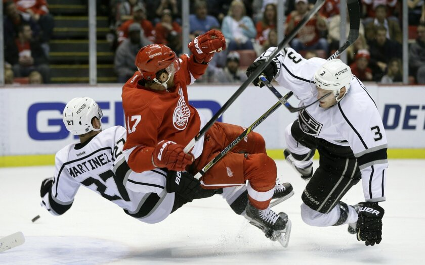 Detroit Red Wings center Brad Richards (17) collides with Los Angeles Kings defensemen Alec Martinez (27) and Brayden McNabb (3) in front of the net during the second period of an NHL hockey game, Friday, Nov. 20, 2015, in Detroit. (AP Photo/Carlos Osorio)