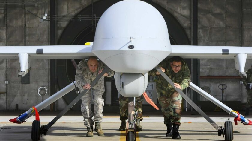 Google recently decided not to renew a contract to use artificial intelligence to analyze drone footage. Above, members of the California National Guard push a Predator aircraft from its hangar at George Air Base in Victorville.