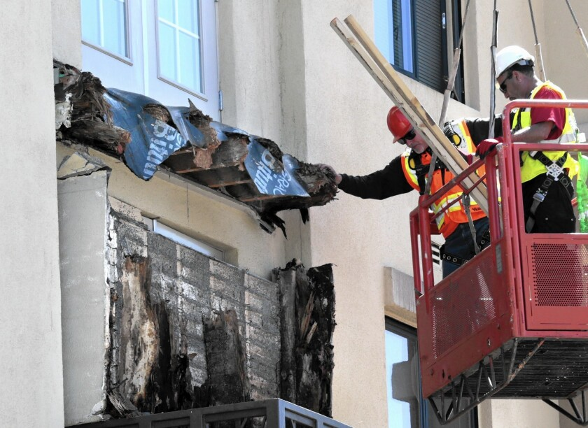 Construction crews remove pieces of a balcony that collapsed in Berkeley, exposing what appears to be dry rot lumber. The collapse killed six people and injured seven a few blocks from UC Berkeley.