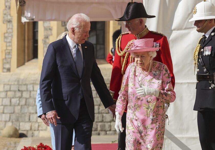 Biden reaches out a hand to Queen Elizabeth, followed by British military men in uniform.