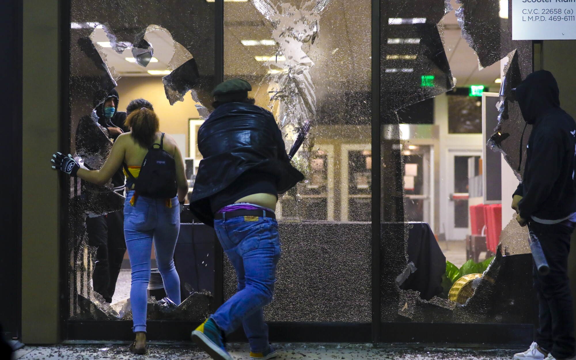 Looters smash windows at the Union Bank on Spring Street in La Mesa, before eventually setting it on fire.