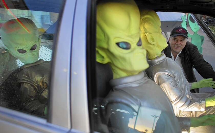 """Luis Ramallo, owner of Alien Fresh Jerky in Baker, Calif., checks out aliens inside a """"Back to the Future""""-type car in front of his store. Ramallo wants to build a UFO-themed hotel to try to breathe some life back into the struggling desert town, whose biggest tourist attraction is a giant thermometer that's now gone dark."""