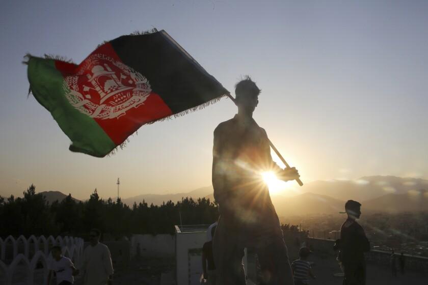 Un hombre ondea una bandera nacional afgana durante las celebraciones del Día de la Independencia en Kabul, Afganistán.