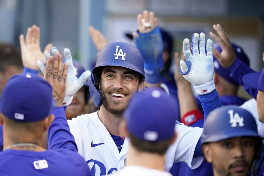 Los Angeles Dodgers' Cody Bellinger, center, smiles in the dugout after his grand slam against the St. Louis Cardinals during the first inning of a baseball game Wednesday, June 2, 2021, in Los Angeles. (AP Photo/Marcio Jose Sanchez)