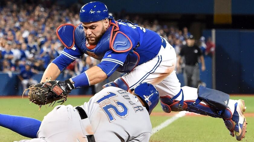 Russell Martin, shown trying to tag Rougned Odor of the Rangers in 2015, began his major league career with the Dodgers.