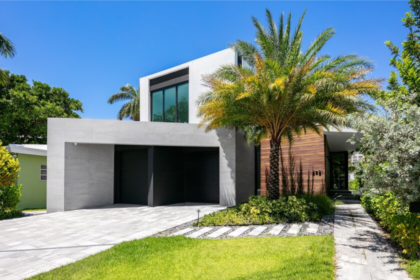 Set on Sunset Lake, the modern home built in 2019 includes a movie theater, swimming pool and private concrete dock.