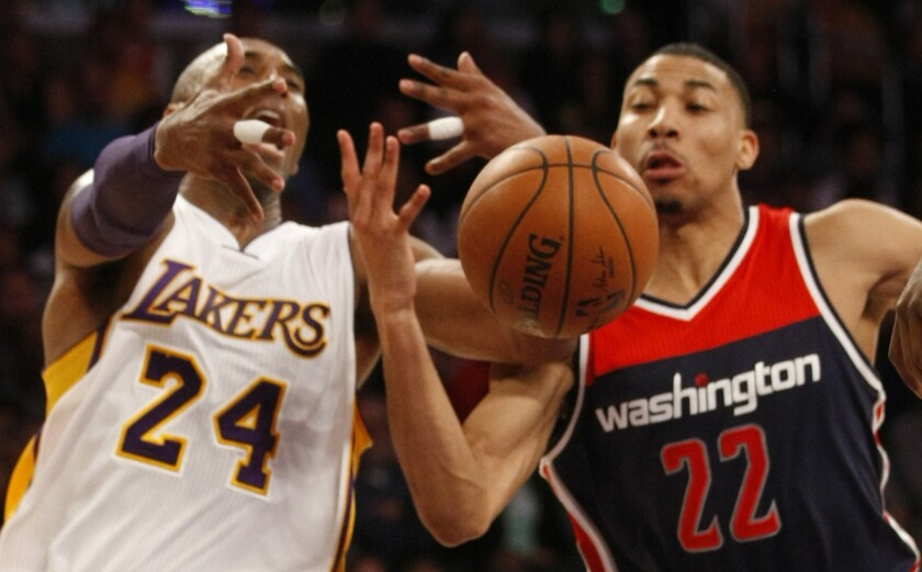 Lakers forward Kobe Bryant loses control of the ball against the defense of Wizards forward Otto Porter Jr.