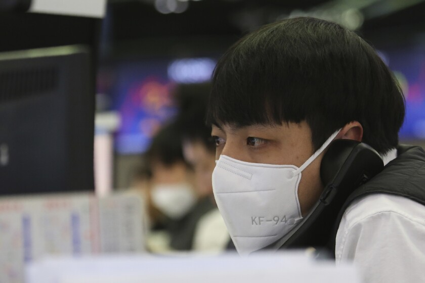 A currency trader talks on the phone at the foreign exchange trading room of the KEB Hana Bank headquarters in Seoul, South Korea, Tuesday, Feb. 4, 2020. Shares advanced in Asia on Tuesday, with the Shanghai Composite up 0.2% after a rebound on Wall Street overnight. (AP Photo/Ahn Young-joon)