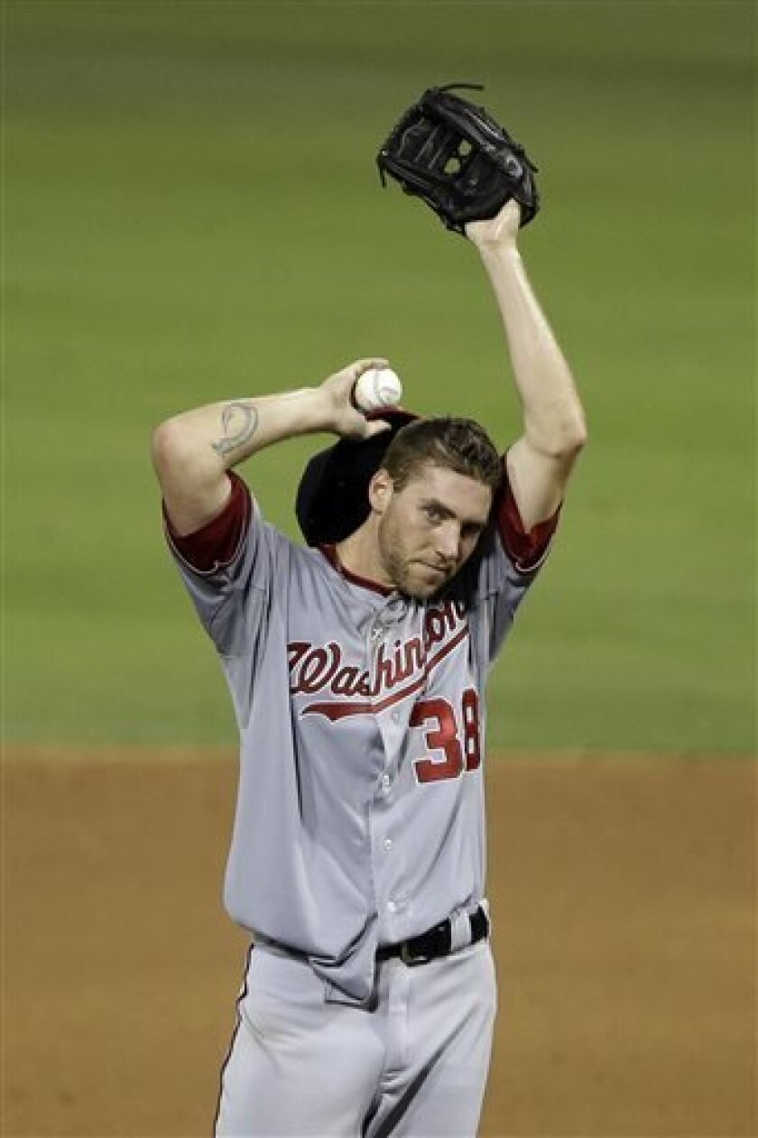 Washington Nationals starting pitcher Taylor Jordan wipes his face after giving up a two-run double to Philadelphia Phillies' Michael Young in the sixth inning of a baseball game, Tuesday, July 9, 2013, in Philadelphia. Young was thrown out trying to advance to third. Philadelphia won 4-2. (AP Photo/Matt Slocum)