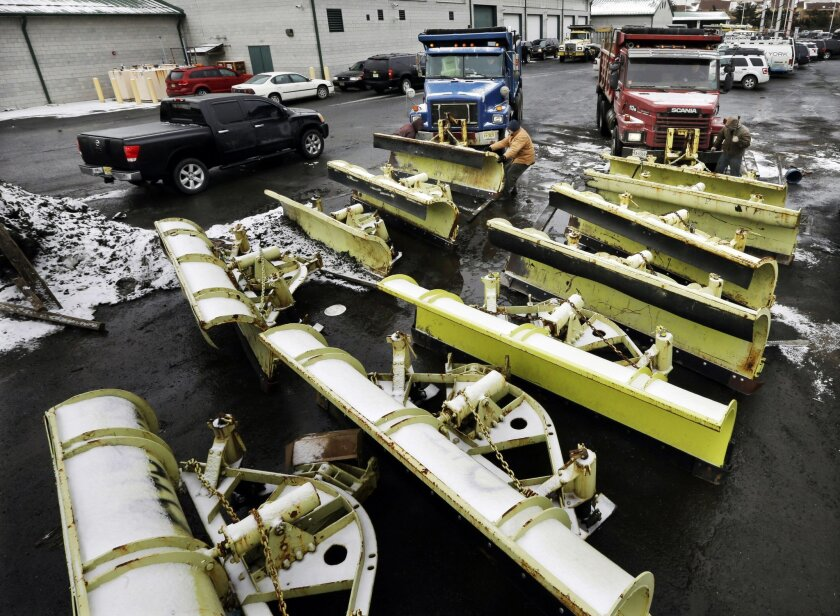 Workers attach snow plows to trucks at a New Jersey Dept. of Transportation maintenance yard, Monday, Jan. 26, 2015, in Newark, N.J. New Jersey Gov. Chris Christie declared a state of emergency saying NJ Transit will shut down late Monday as a winter storm threatens to dump as much as two feet of s