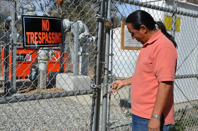 Vincent Marruffo inspects a lock on a fence around a sewer pump station built on his family's property by the Pala tribe without permission.