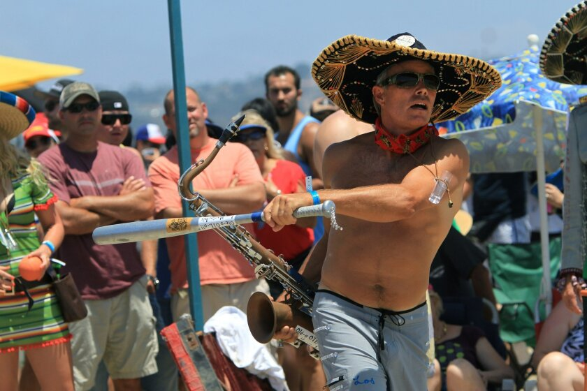 Baseball bat in one hand and saxophone Roberto Ruane of the team Los Mariachis de OTL takes a swing during the Over-The-Line Tournament at Fiesta Island Saturday. photo by Bill Wechter