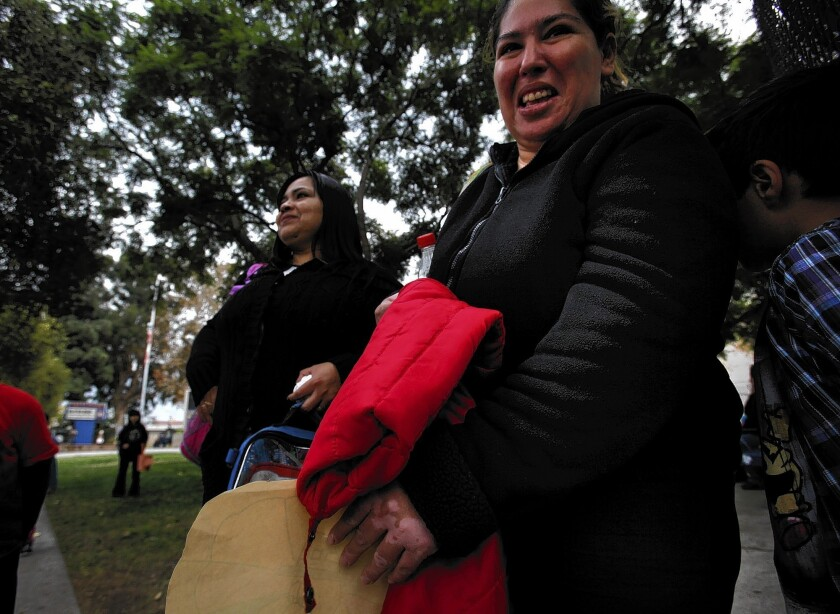 Adelina Garcia, left, and Adriana Serrano walk their children home from Teresa Hughes Elementary School in Cudahy. They were parent leaders in a petition drive last fall to oust the school principal.