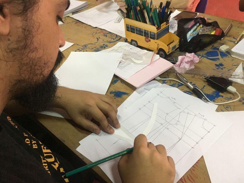 Max Milliano Melo, un estudiante en la clase de costura de Casa 1, aprende a dibujar un molde (Jill Langlois / para Los Angeles Times).