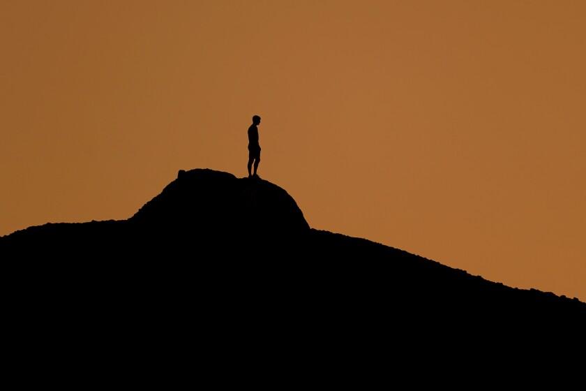 Un hombre observa solo el atardecer en una colina del Papago Park de Phoenix el 19 de febrero
