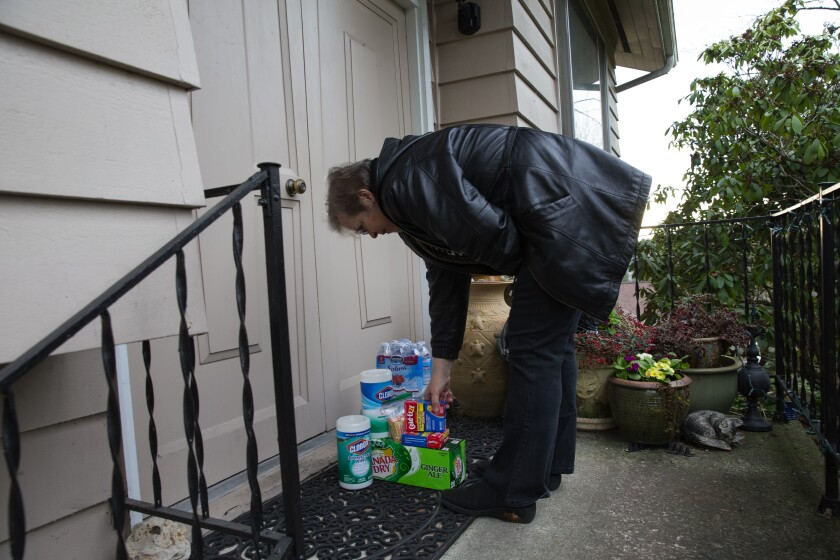 Cheri Chandler drops off disinfectants, throat lozenges and ginger ale for her parents, Pat and Bob McCauley, who are self-quarantined at their home in Kirkland, Wash., on March 10, 2020.