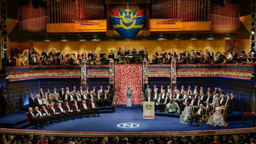 The 2016 Nobel laureates in literature, medicine, chemistry, physics and economics are seated, front row left across from King Carl XVI Gustaf of Sweden and the royal family.