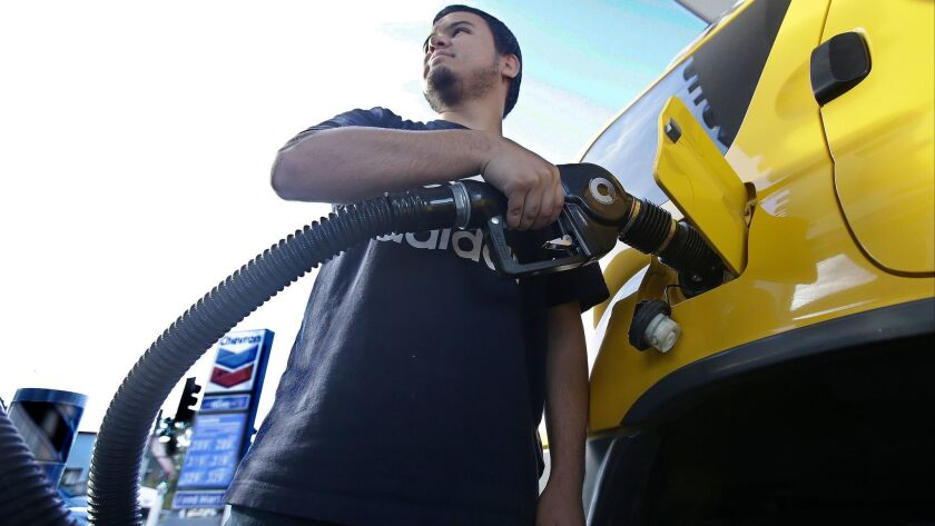 Cristian Rodriguez fuels his vehicle in Sacramento. Gasoline taxes rose by 12 cents per gallon Wednesday to raise money for fixing roads and highways. It is the first of several tax and fee hikes that will take effect after they were approved by the Legislature.