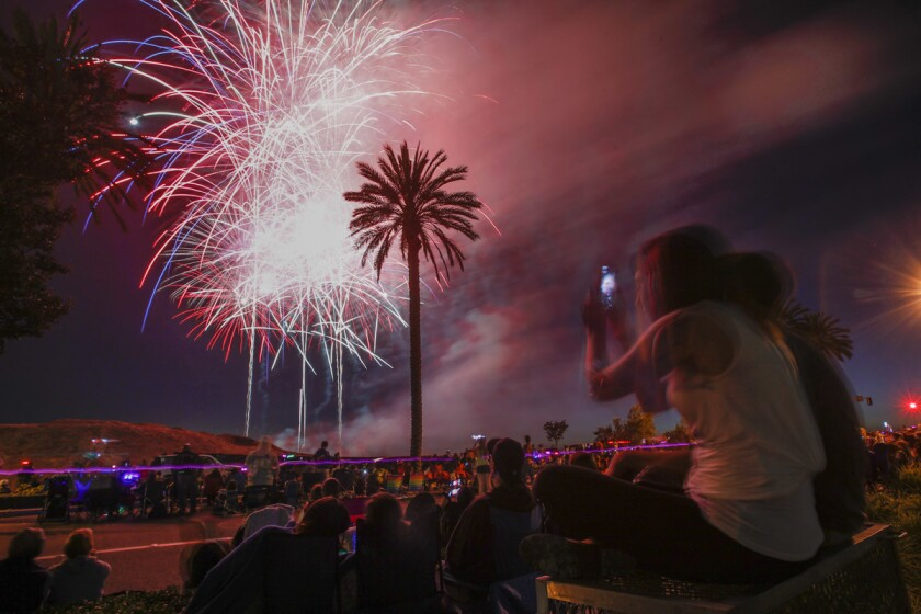 Jessica Gandarillas records with her phone as she and Marine Lance Cpl. Matt Lewandowski watch the fireworks display.