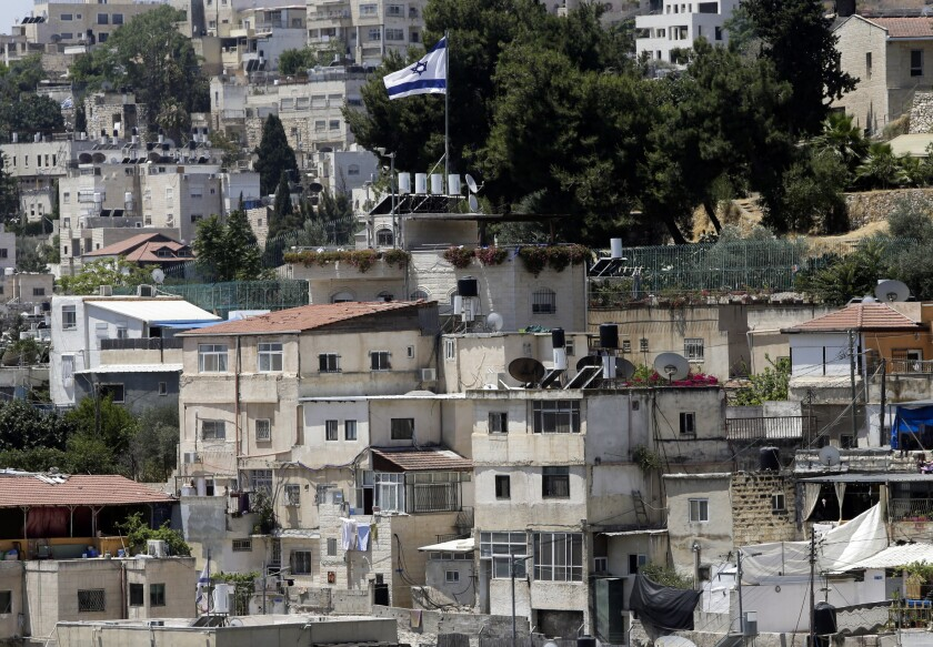 "An Israeli flag flies over a Jewish owned house in a Palestinian neighborhood of Silwan in east Jerusalem, Wednesday, July 1, 2020. Israeli leaders paint Jerusalem as a model of coexistence, the ""unified, eternal"" capital of the Jewish people, where minorities have equal rights. But Palestinian residents face widespread discrimination, most lack citizenship and many live in fear of being forced out. (AP Photo/Mahmoud Illean)"