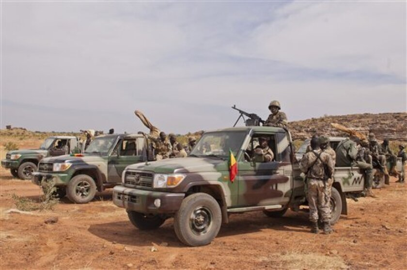 """In this Nov. 24, 2012 photo, soldiers from a Malian army special unit stand atop pick-ups mounted with machine guns, following a training exercise in the Barbe military zone, in Mopti, Mali. Secretary-General Ban Ki-moon said Friday, Jan. 11, 2013, that France, Senegal and Nigeria have responded to an appeal from Mali's President Dioncounda Traore for help to counter an offensive by al-Qaida-linked militants who control the northern half of the country and are heading south. The U.N. chief said that assisting the Malian defense forces push back against the Islamist armed groups is """"very important.""""(AP Photo/Francois Rihouay)"""