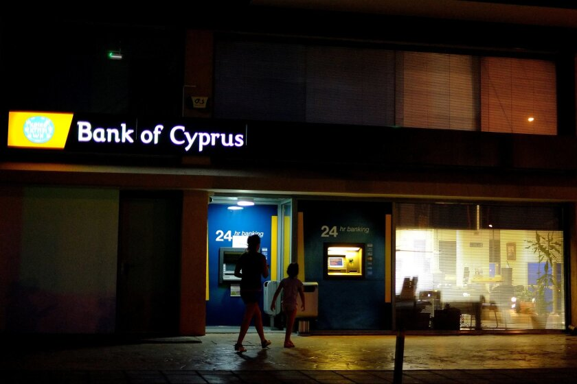 A woman and a girl walks outside a branch of Bank of Cyprus in capital Nicosia, Cyprus, Wednesday Sept. 10, 2014. The European Union warned Cyprus Wednesday that it may be flouting the terms of its multibillion-euro rescue package after the country's parliament approved legislation softening a crucial foreclosures law. (AP Photo/Petros Karadjias)