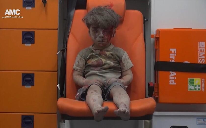 En esta imagen, tomada de un video distribuido por el grupo opositor sirio Aleppo Media Center (AMC), aparece un niño sentado en una ambulancia tras ser rescatado de entre los escombros de un edificio alcanzado por un bombardeo aéreo en Alepo, Siria, el 17 de agosto de 2016. (Aleppo Media Center via AP)