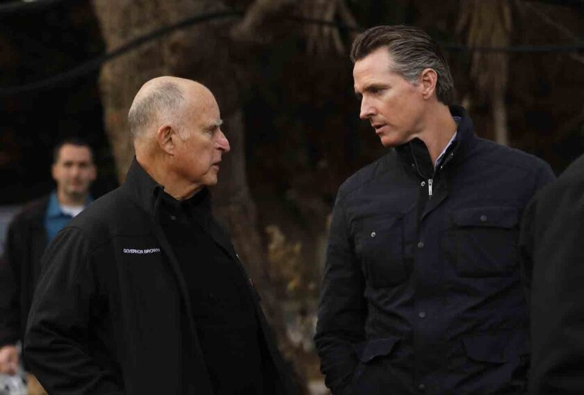 Gov. Gavin Newsom, right, and the man he replaced, Jerry Brown have a conversation, last November in Malibu. Newsom has heeded Brown's warning about the risk of adding new spending programs when state revenue is so unpredictable.