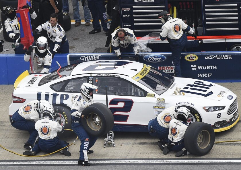 Sprint Cup Series driver Brad Keselowski (2) gets new tires a fuel in the pits during the NASCAR Sprint Cup Series auto race at Talladega Superspeedway, Sunday, Oct. 25, 2015, in Talladega, Ala. (AP Photo/Mark Almond)