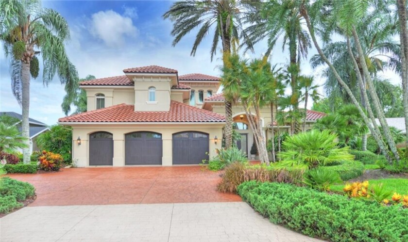 Custom-built in 2002, the four-bedroom home opens to a massive lanai with electric shutters.