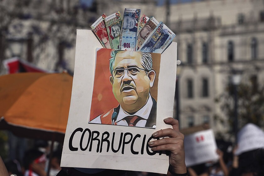 """A protester holds an image of Peruvian leader Manuel Merino with the Spanish word for """"corruption."""""""
