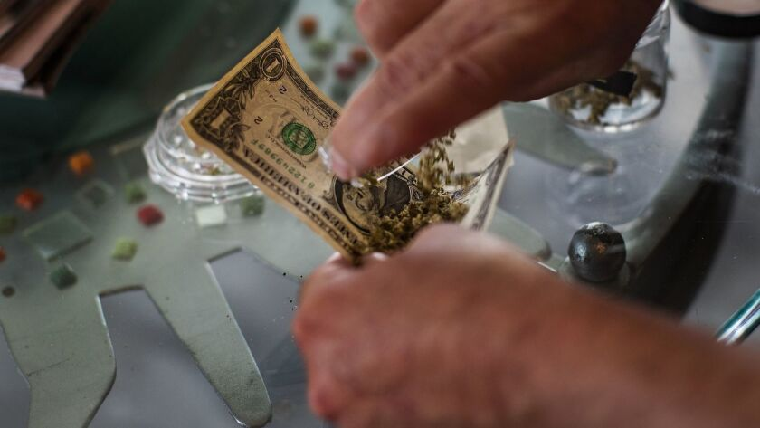 El hotelero John Thatcher usa un billete de un dólar para hacer un cigarro de marihuana en el hotel Desert Hot Springs Inn. (Gina Ferazzi / Los Angeles Times)