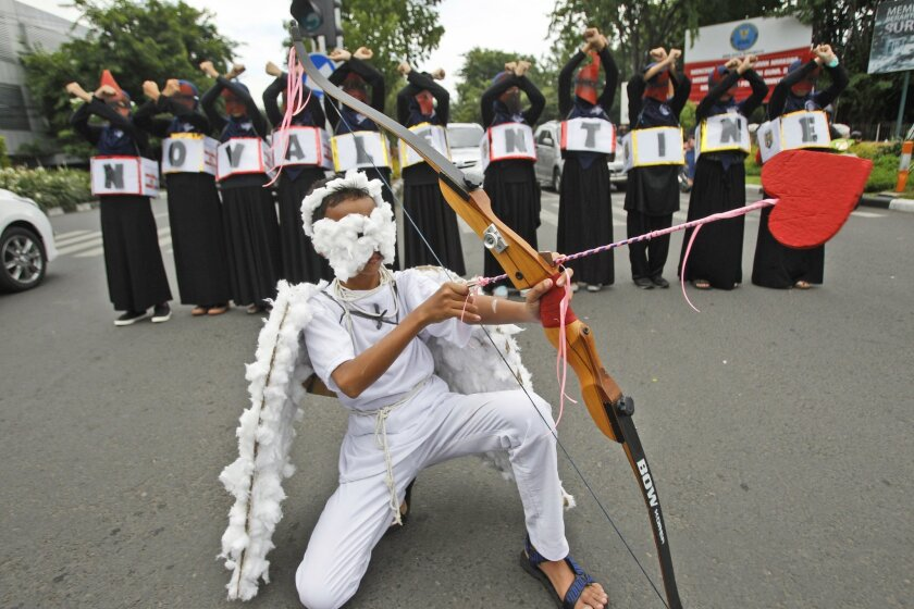A Muslim student dressed as Cupid takes part in a protest against Valentine's Day in Surabaya, East Java, Indonesia, Saturday, Feb. 13, 2016. Dozens of students staged the protest calling on Muslims to avoid the celebration of the western holiday, saying that it's against Islamic teachings and coul