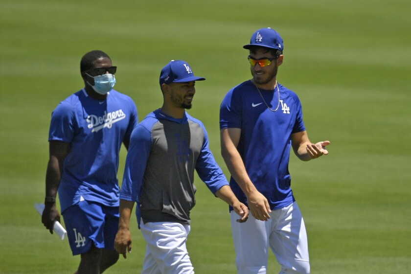 Los Angeles Dodgers right fielder Mookie Betts, center, and center fielder Cody Bellinger, right, chat during the restart of baseball spring training Saturday, July 4, 2020, in Los Angeles. (AP Photo/Mark J. Terrill)