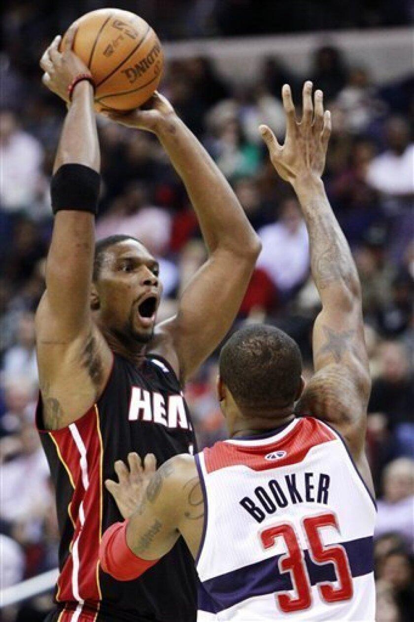 Miami Heat forward Chris Bosh (1) looks to make a pass around Washington Wizards forward Trevor Booker (35) in the first quarter of an NBA basketball game in Washington, Friday, Feb. 10, 2012. (AP Photo/Jacquelyn Martin)