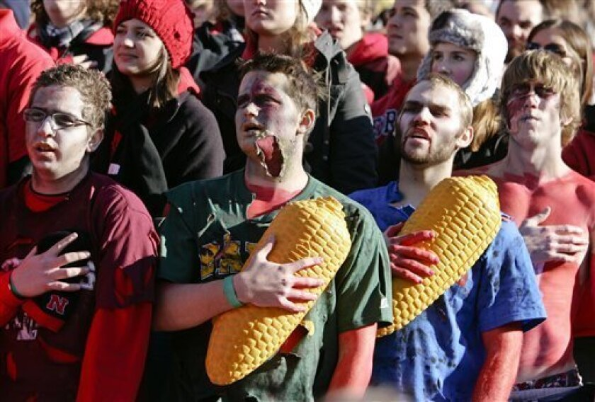 """Nebraska fans hold their corn hats to their chests during the singing of the """"Star Spangled Banner"""" prior to an NCAA college football game against Colorado, in Lincoln, Neb., Friday, Nov. 26, 2010. (AP Photo/Nati Harnik)"""