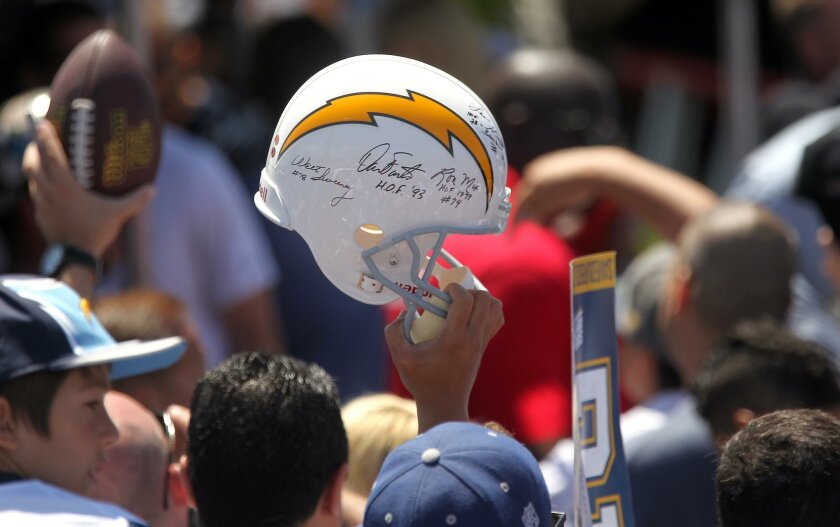 Fans hold up items to be signed by Chargers quarterback Philip Rivers after the rally.