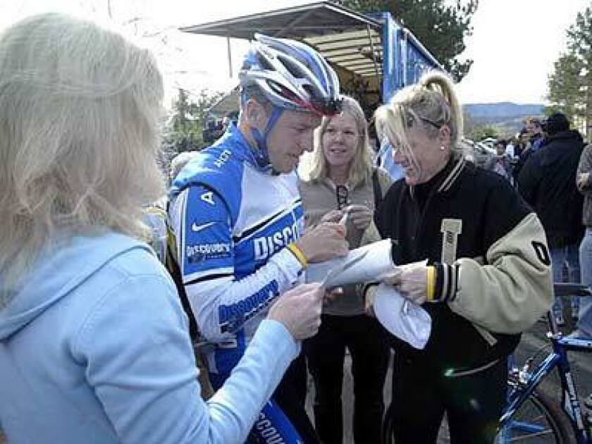 Lance Armstrong is surrounded by autograph seekers before heading out on a 100-mile training ride with his teammates around Solvang.