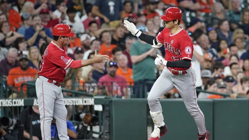 The Angels' Shohei Ohtani is congratulated by third base coach Mike Gallego after connecting for a third-inning home run against the Astros on Friday night.