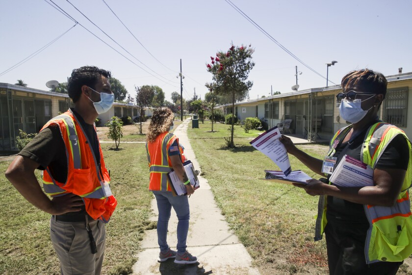 Healthcare works go door to door to educate people about the importance of COVID-19 vaccination in South Los Angeles.