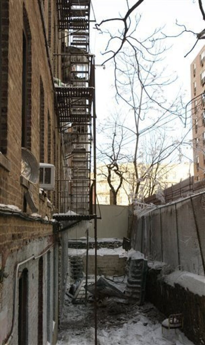 In this Jan. 23, 2005 file photo, debris in the snow below marks the spot where two firefighters were killed and four injured when they jumped from the building at left in an early morning blaze in the Bronx borough of New York. The firefighters were trapped in a burning maze of illegal partitions