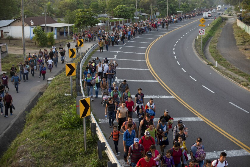 Central American migrants, part of the caravan hoping to reach the U.S. border, walk on the shoulder