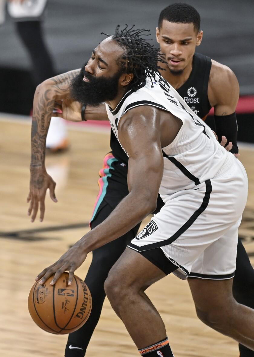 James Harden, de los Nets de Brooklyn, recibe una falta de Dejounte Murray, de los Spurs de San Antonio, en la primera mitad del juego del lunes 1 de marzo de 2021, en San Antonio. (AP Foto/Darren Abate)