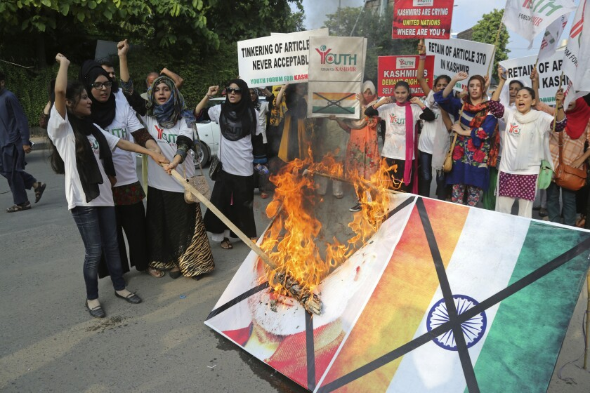 Pakistani students in Lahore burn a poster of Indian Premier Narendra Modi