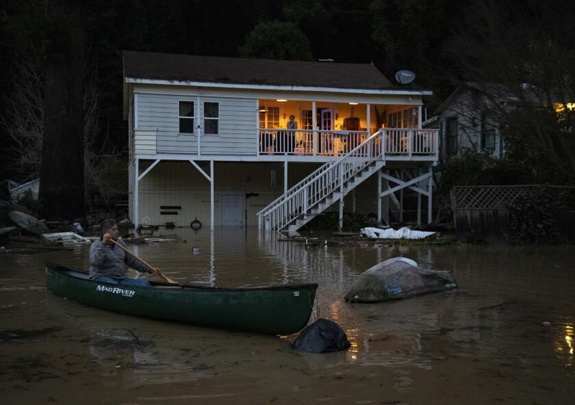 Richard López, de Río Nido, California, usa una canoa para recuperar su moto acuática, que flotaba en las aguas de la inundación frente a su casa en el Russian River Valley.