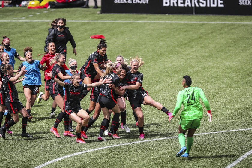 Portland Thorns teammates swarm Morgan Weaver (22) after she made the game-winning penalty kick during the NWSL Challenge Cup soccer final against NJ/NY Gotham FC at Providence Park, Saturday, May 8, 2021, in Portland, Ore. (Serena Morones/The Oregonian via AP)