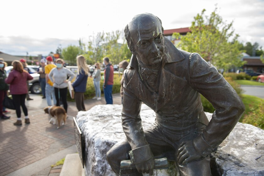 The Alexander Baranof statue, pictured with a patina of bird droppings in front of Harrigan Centennial Hall, was at the center of a protest Tuesday, June 23, 2020, just prior to a city Assembly meeting in Sitka, Alaska. An Alaska city assembly voted Tuesday, July 14, 2020, to relocate the statue of a Russian merchant that has drawn criticism as a symbol of colonialism and abuse of the region's Indigenous people. (James Poulson/Daily Sitka Sentinel via AP)