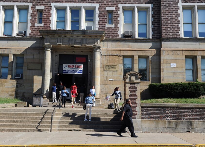 A security guard patrols in front of Wilkinsburg High School in Wilkinsburg, Pa., Monday, Sept. 21, 2015, after students were released from school because a student poured gasoline on a security guard. A spokesman for a Pennsylvania school district says the student attacked a security guard by pouring gasoline hidden inside a soda bottle on him. The spokesman says the student poured the fuel on the guard and the floor after 9 a.m. but didn't light it. The student is in police custody. The guard isn't believed to be seriously injured. (Nate Guidry/Pittsburgh Post-Gazette via AP) MAGS OUT; NO SALES; MONESSEN OUT; KITTANNING OUT; CONNELLSVILLE OUT; GREENSBURG OUT; TARENTUM OUT; NORTH HILLS NEWS RECORD OUT; BUTLER OUT; MANDATORY CREDIT