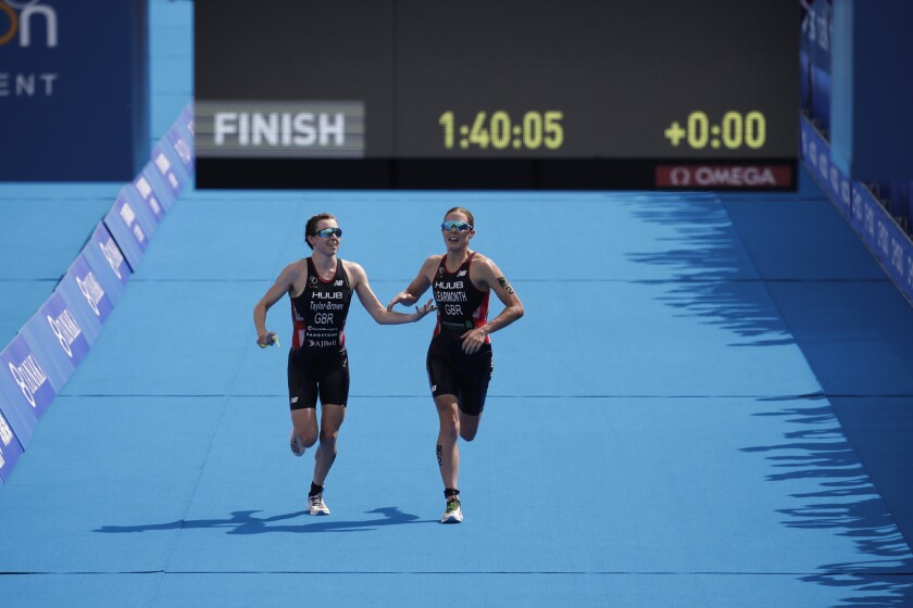 Georgia Taylor-Brown, left, and Jessica Learmonth join hands as they run toward the finish line.